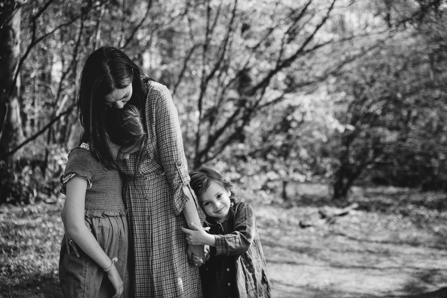 A mother holds her two daughters close for hugging them together
