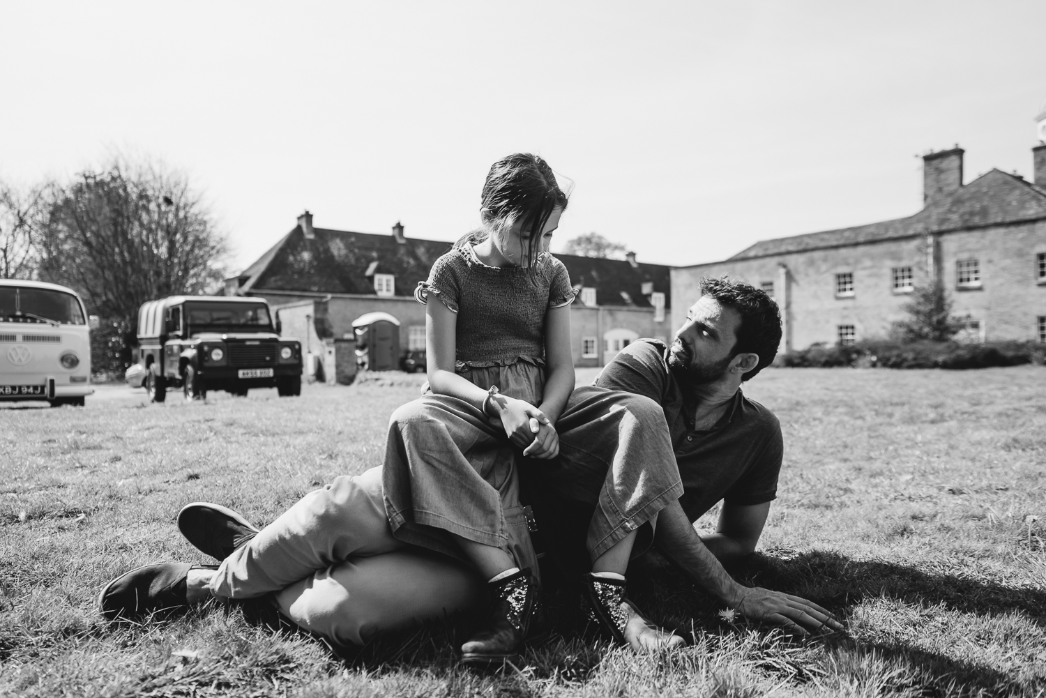 Black and white photograph of a father and daughter relaxing on the grass in the grounds of Wandlebury Country Park, Cambridgeshire