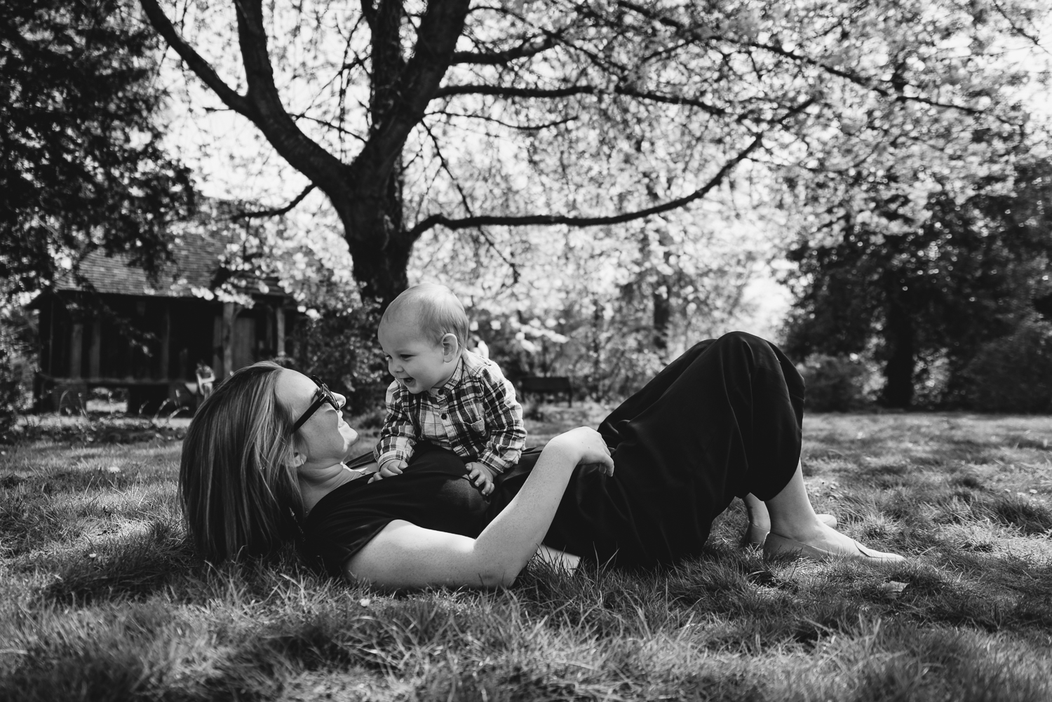 Black and white photograph of a mother and baby relaxing together under the shade of a cherry blossom tree in Wandlebury country park, Cambridge