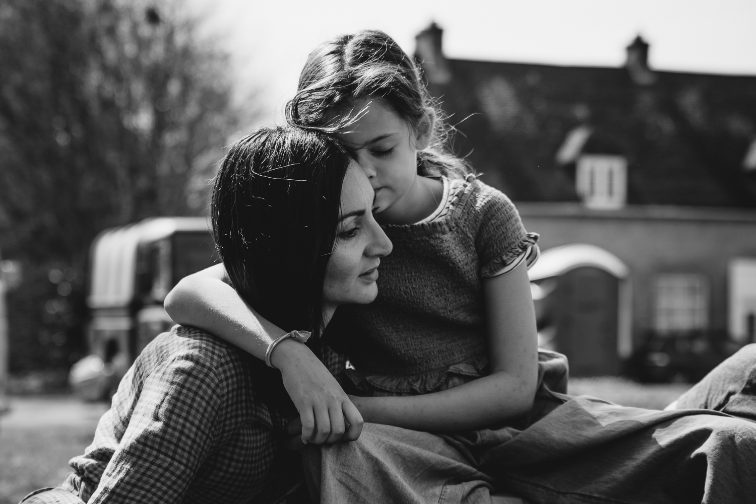 A girl tenderly presses her face against her mother in a black and white photograph taken by Cambridge family photographer Diana Hagues