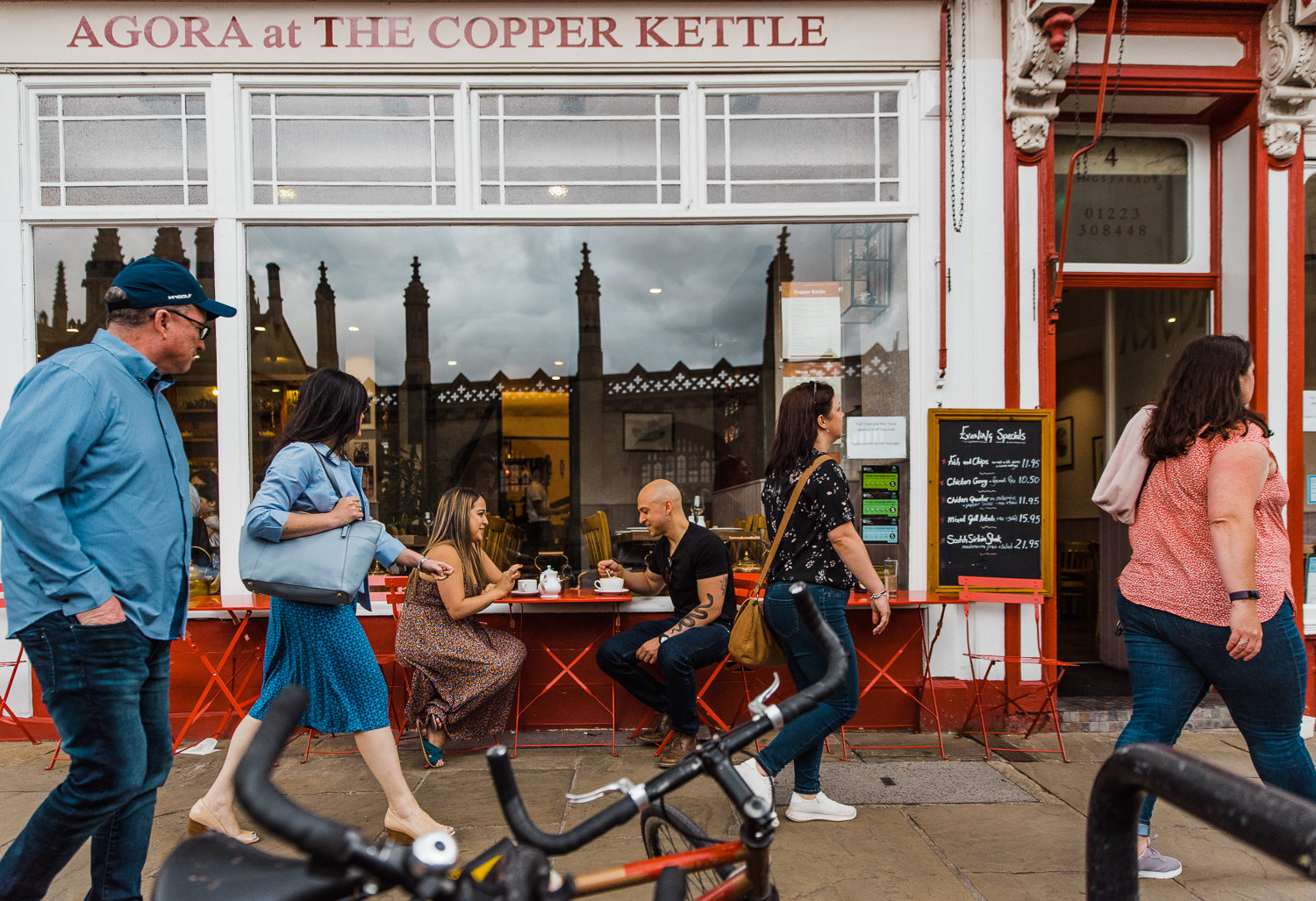 A couple sits outside drinking tea at The Copper Kettle in Cambridge as people walk by