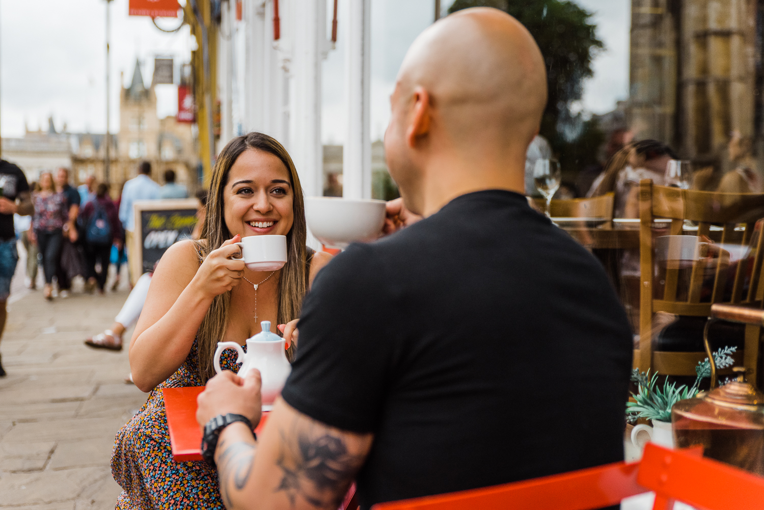 A woman drinks tea while smiling at her boyfriend during a couple photo session in Cambridge