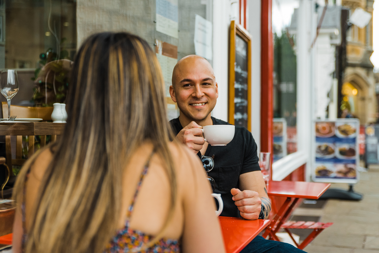 A man drinks coffee while smiling at his girlfriend during a couple photo session in Cambridge