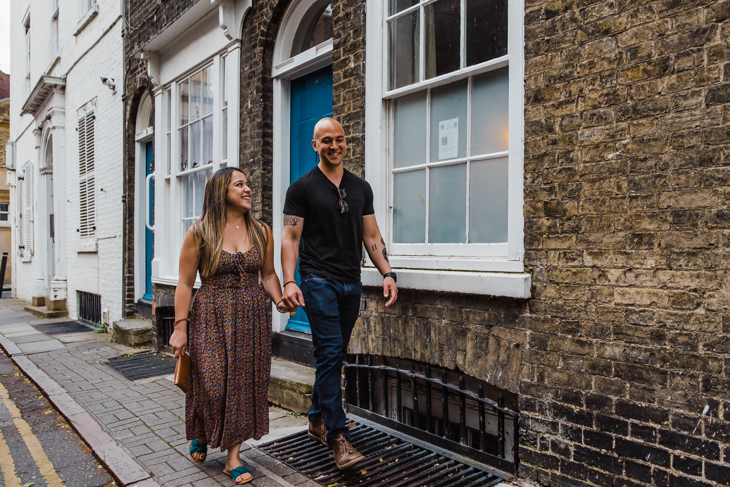 A woman walking hand-in-hand during an engagement session in Cambridge with photographer Diana Hagues Photography