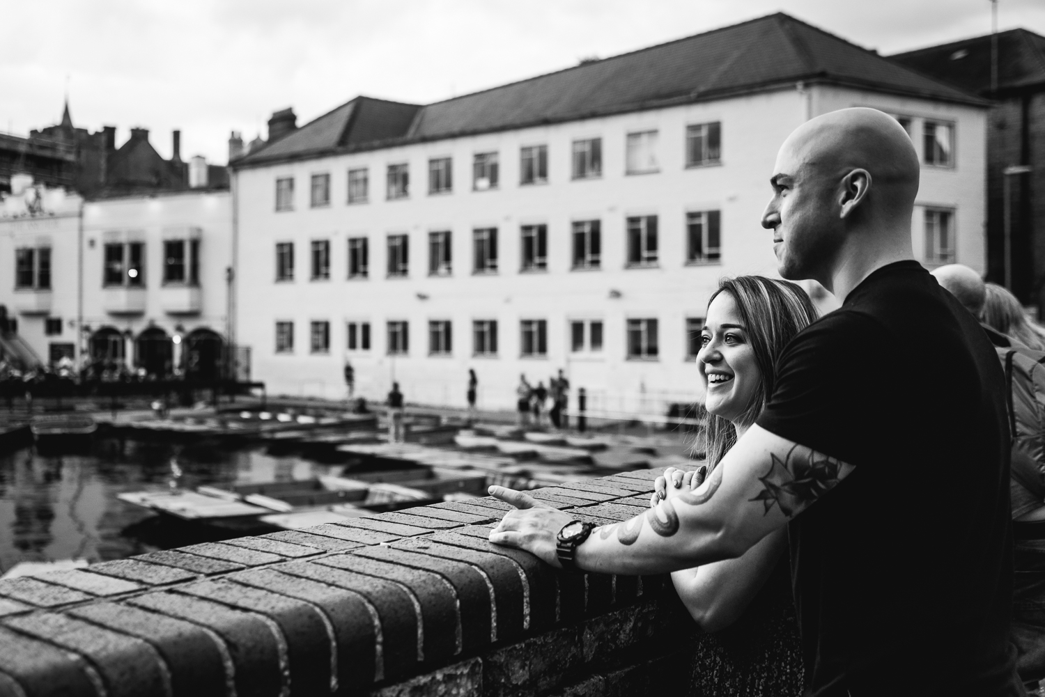 Black and white photograph of a couple looking out across the River Cam at Scudamores