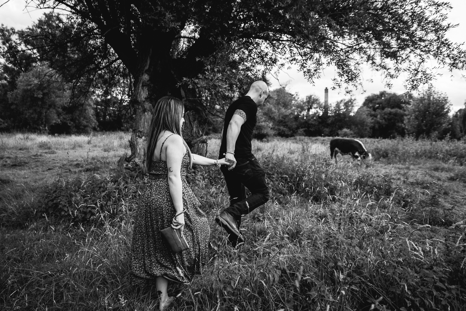 A man takes his girlfriend by the lead in the grassy meadow at Mill Pit, Cambridge