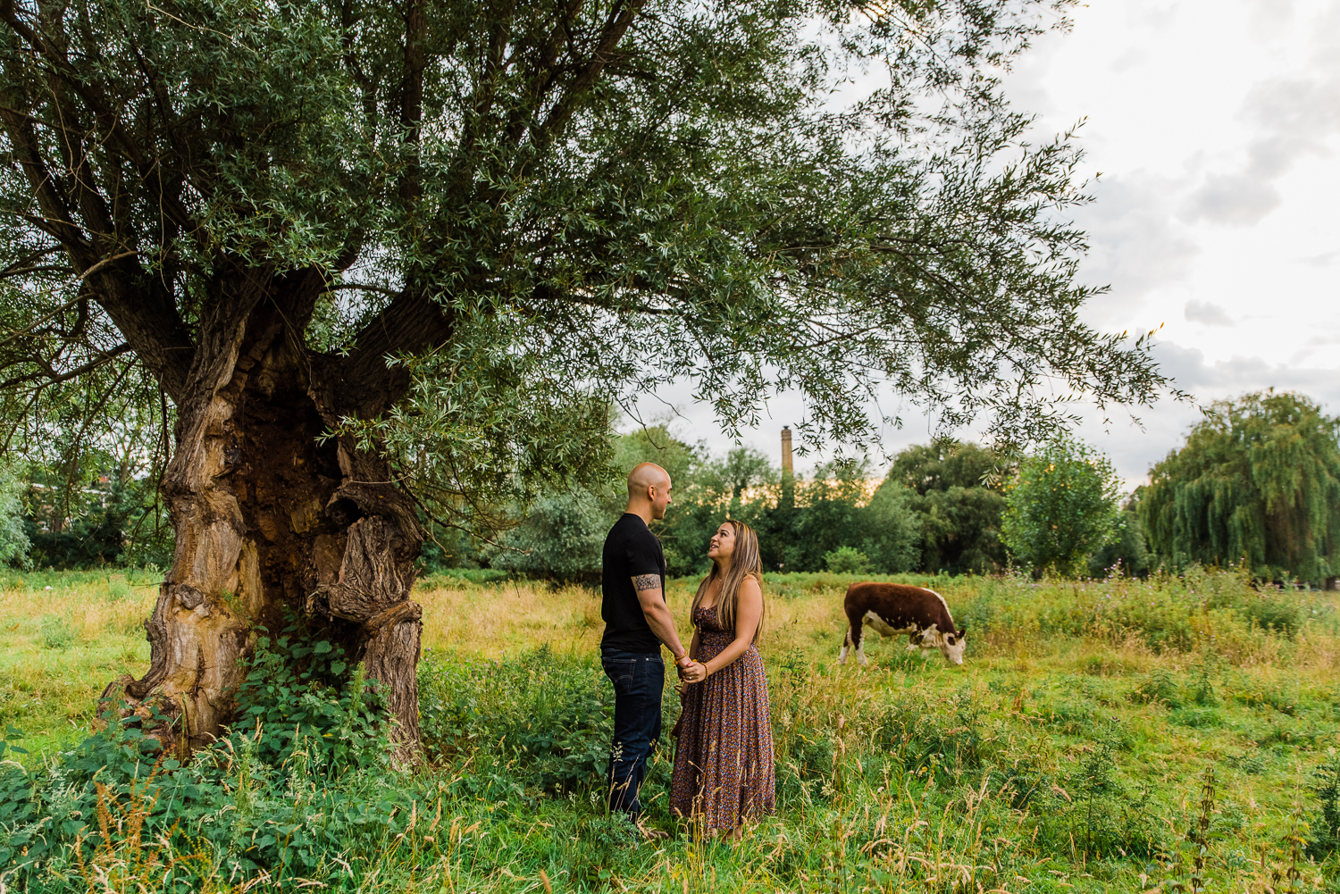 A couple stands under a willow tree during a couple engagement photoshoot in Cambridge