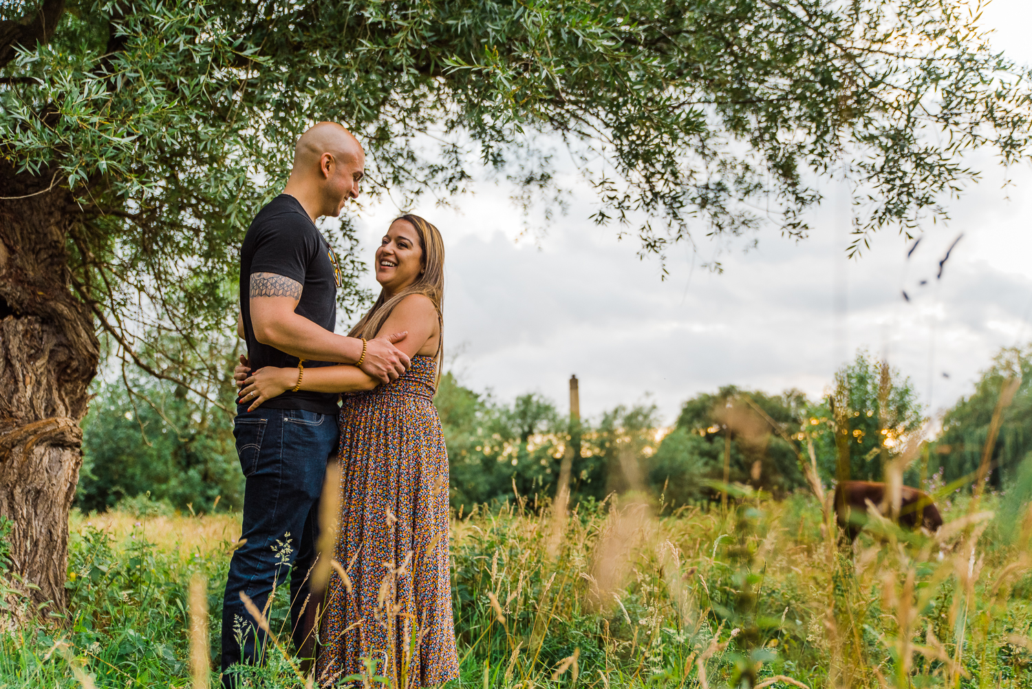 A couple embraces each other in a field in a couple engagement session in Cambridge