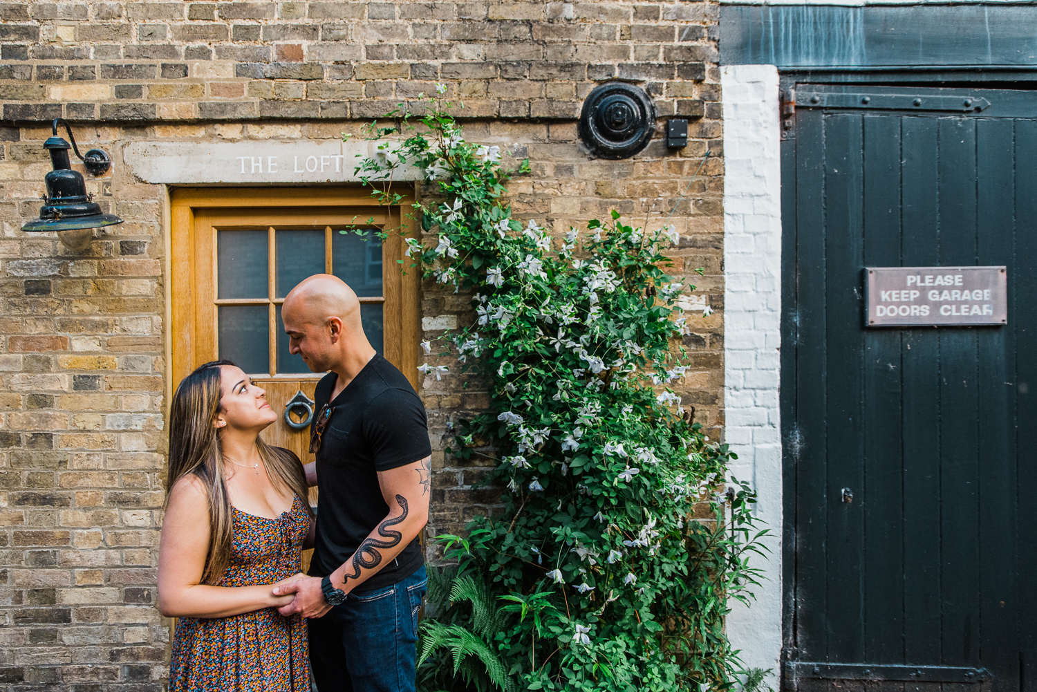 Couple standing in front of a wooden door next to wisteria and a black garage door by Diana Hagues Photography