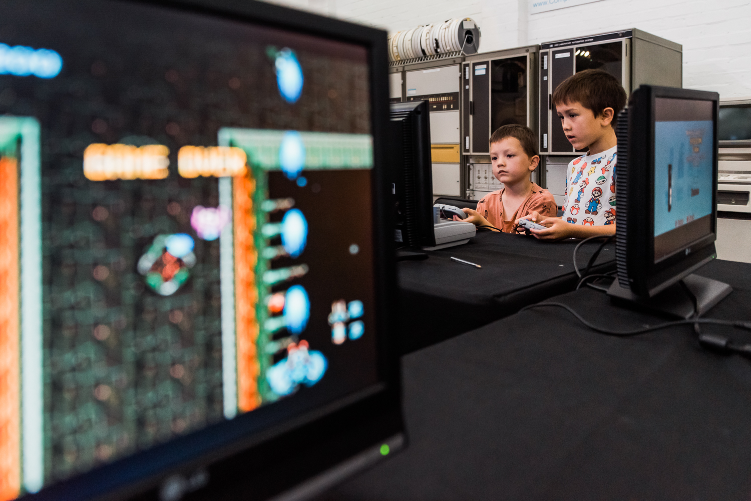 Two children playing computer games inside the Museum of Computing Science