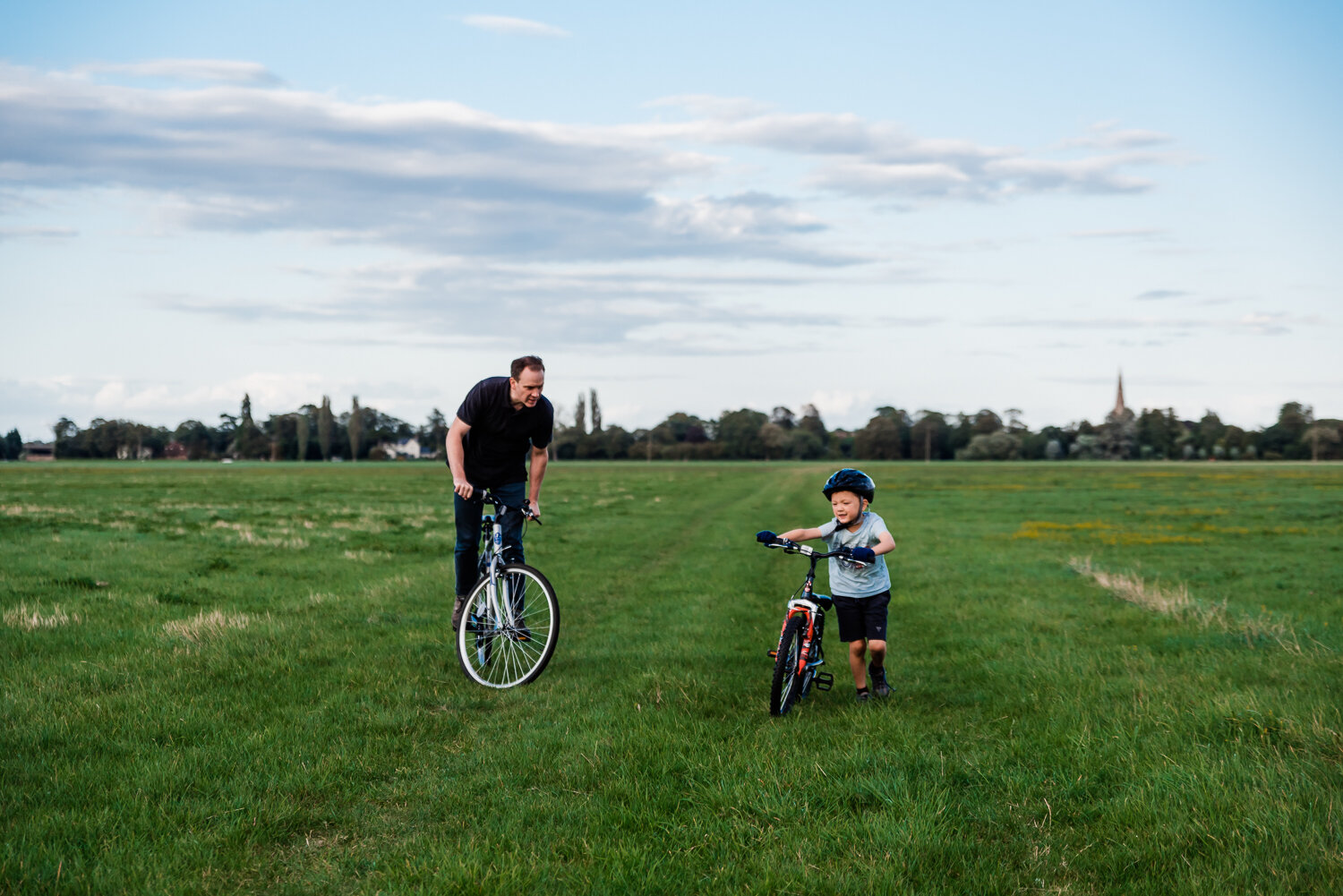 Father and son riding their bikes across a field