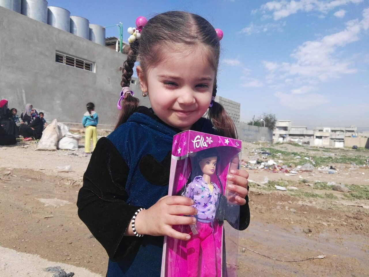 A fulla doll is given to a little girl in W. Mosul while the city is being recovered from ISIS.