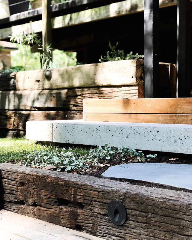 A floating pre cast concrete step adds visual depth and contrast to this design. It sits beautifully against the warmth of the timber, compliments the blue stone steppers as well as the subtle textural contrast to the recycled railway sleepers. We are sticklers for quality and that's why any concrete work is done in house. We are more than just a pretty face here at Tallowood Landscapes! // Design: @mud_landscape_design // 📷Install: @tallowood_landscapes