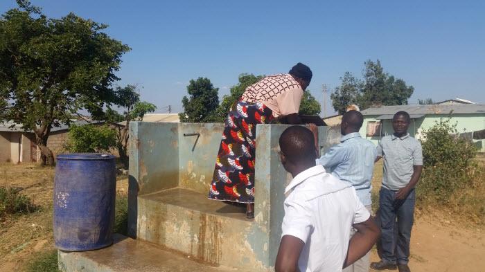 Mary Loukele låser upp en av de statligt reglerade vattenposterna. Mary är utsedd av byrådet att sköta hanteringen av denna vattenpost. Hon tar betalt och håller allmän ordning när vattnet är påslaget.