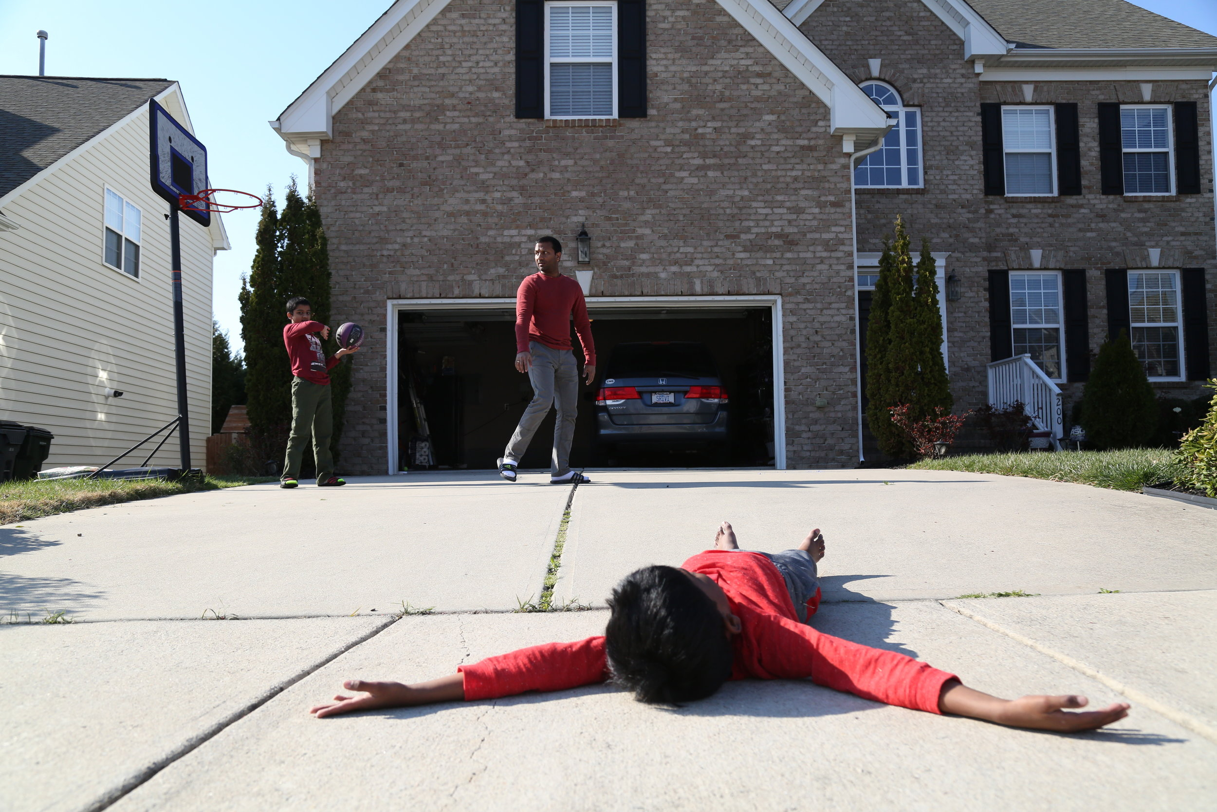 Rajesh Reddy, a native of Morrisville, plays with his two sons, Suresh Reddy (older) and Sirish Reddy (younger) in front of the garage on March.4,2017. The photo was shot as the zipcode assignment for MEJO480, photo stories class.