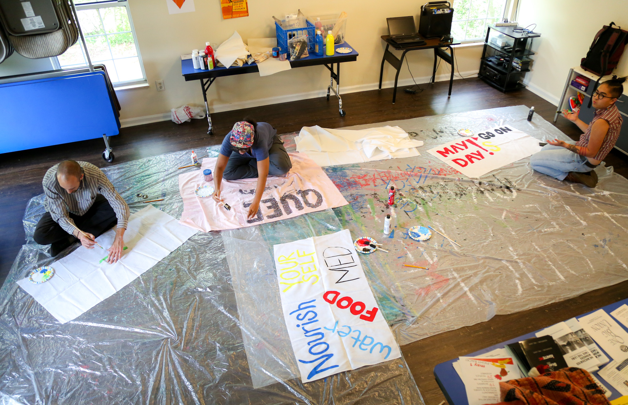 A couple of people show up painting the banners on the floor  for May Day protest at the Southern Vision Alliance office in Durham on April. 22.