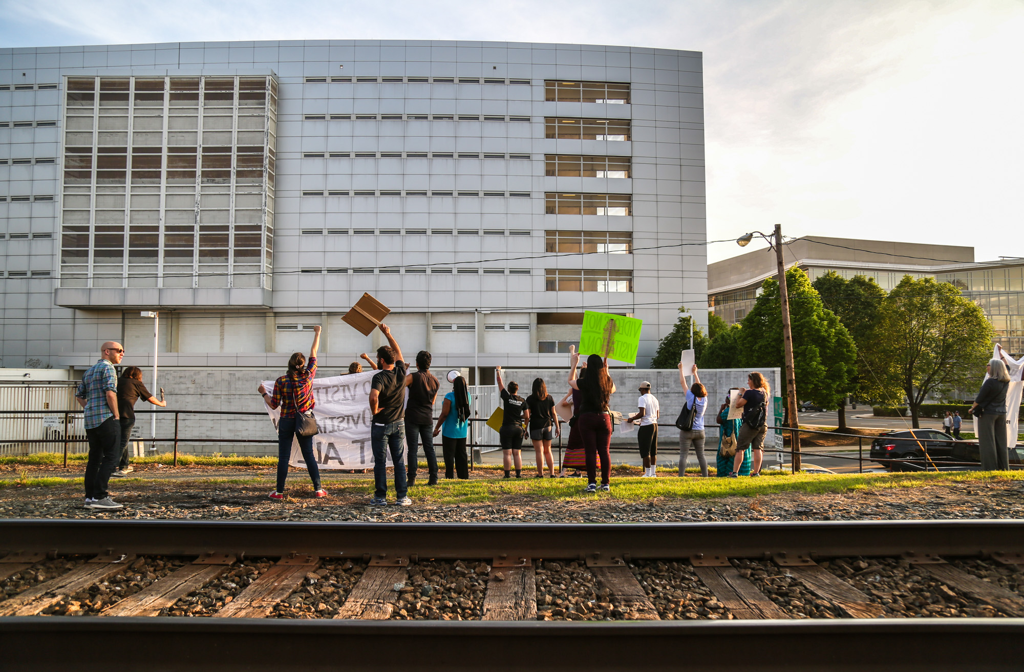 During the protest, people gather in front of the jail, some holding the signs, some writing slogans on the ground with chalks and some holding the speaker. They protest by singing and shouting and sometimes dancing. At the end of the protest, they march down both ends of the street and wave to people up in the bulding.
