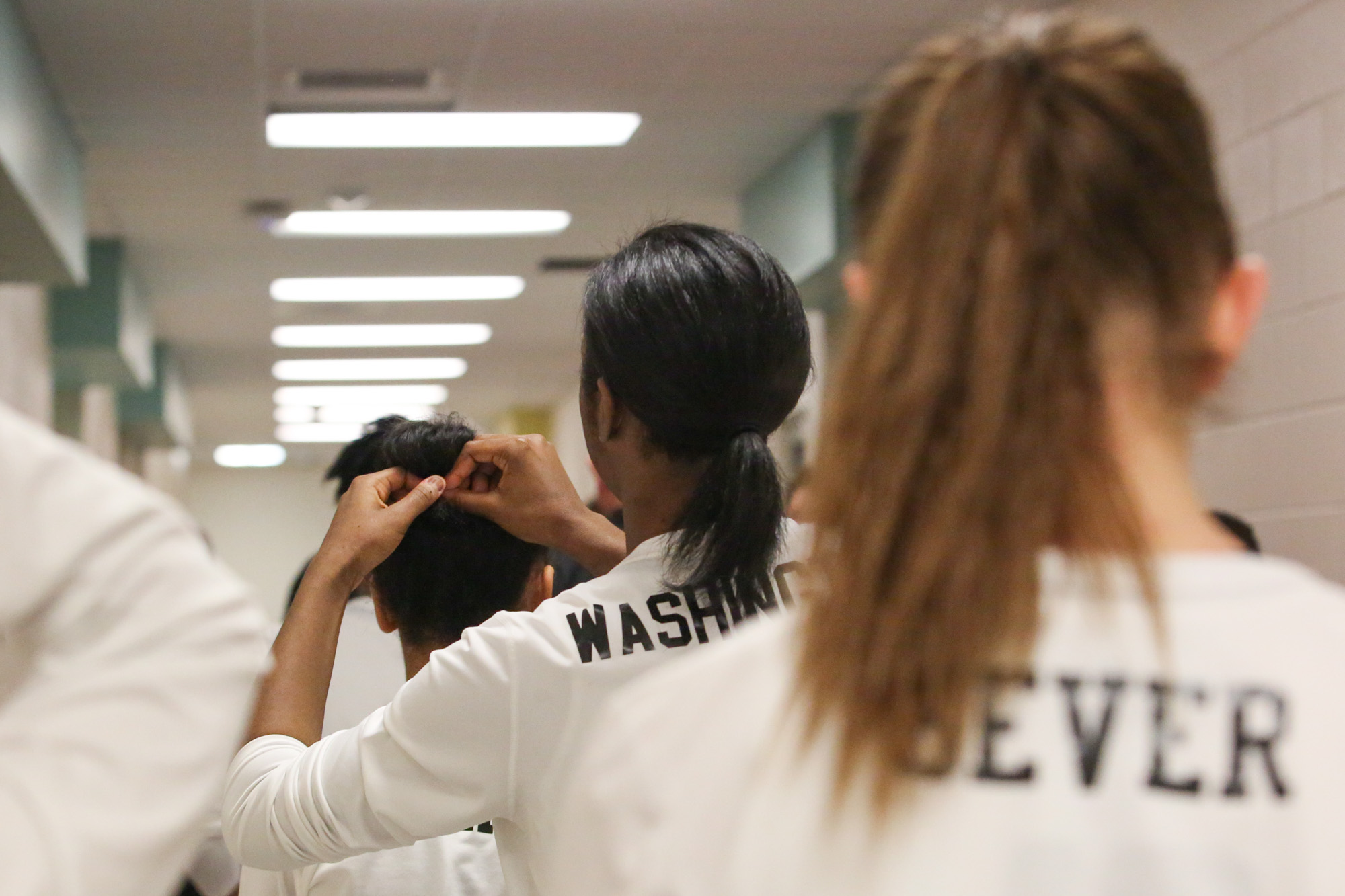 Green Hope's Nia Washington ties the hair up for another player on their way to the basketball gym on Feb.17, 2017.