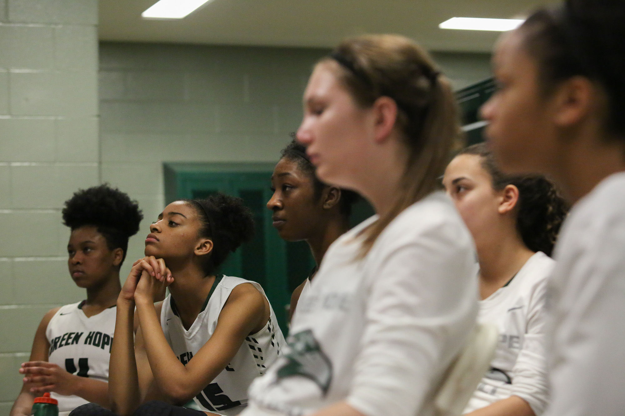 Green Hope girls listen to coach Robinson's instruction on strategies during the half time in the Green Hope's locker room.