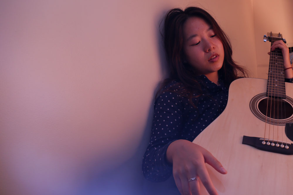 Jiayi Liu holds her guitar in her dorm bed at UNC on Sep.29, 2016.