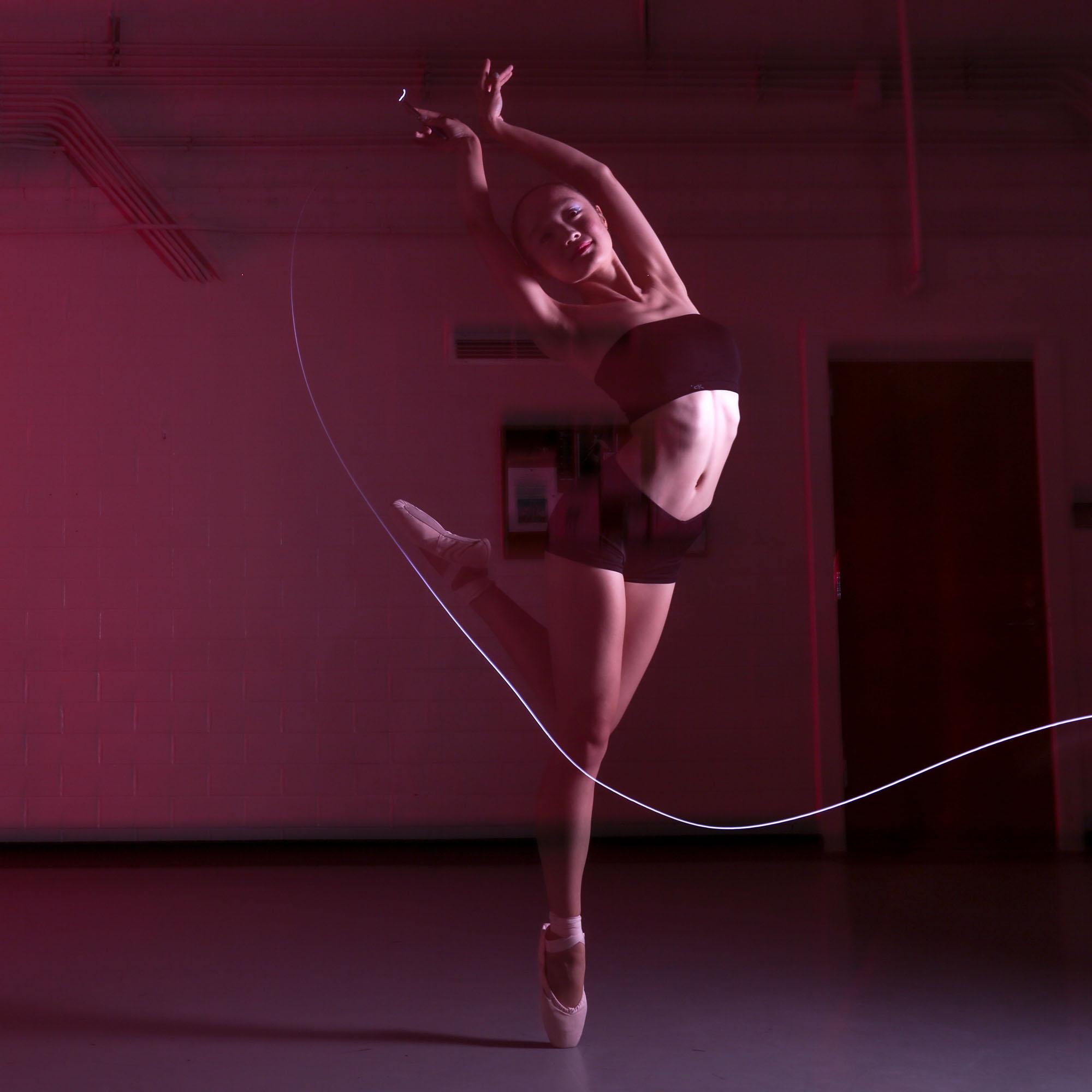 Jinglin Ji holds a flash pen while doing the ballet movement.