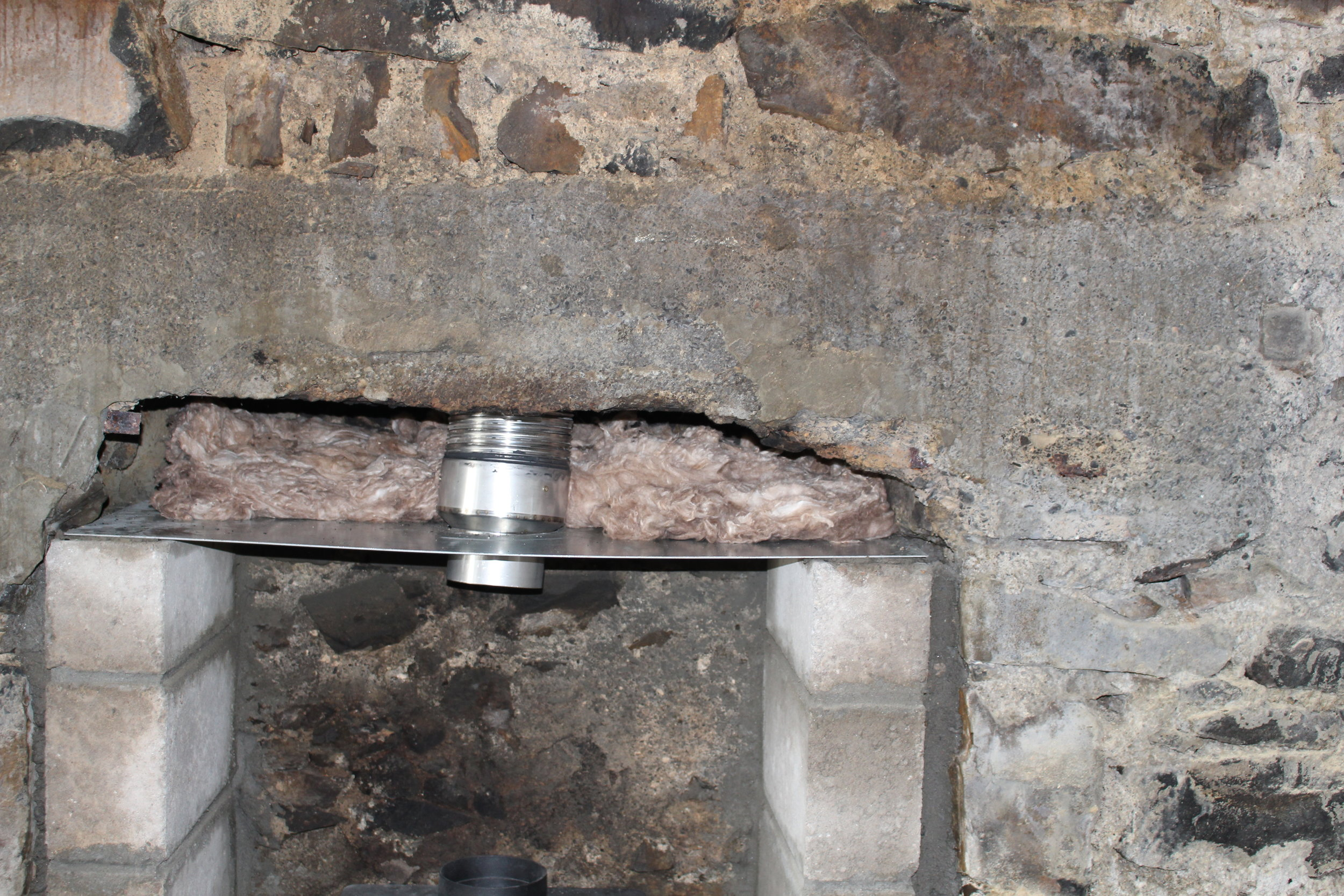 Mineral wool is fitted above the register plate for a couple of reasons: 1. It returns heat from the top of the stove rather than lose it to the chimney, 2. It softens the back-filled vermiculate which is poured from above, down the sides of the flue.