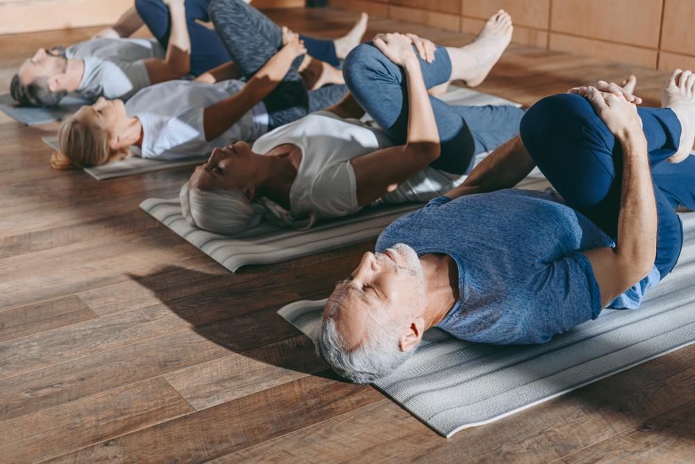 Seniors doing yoga on mat