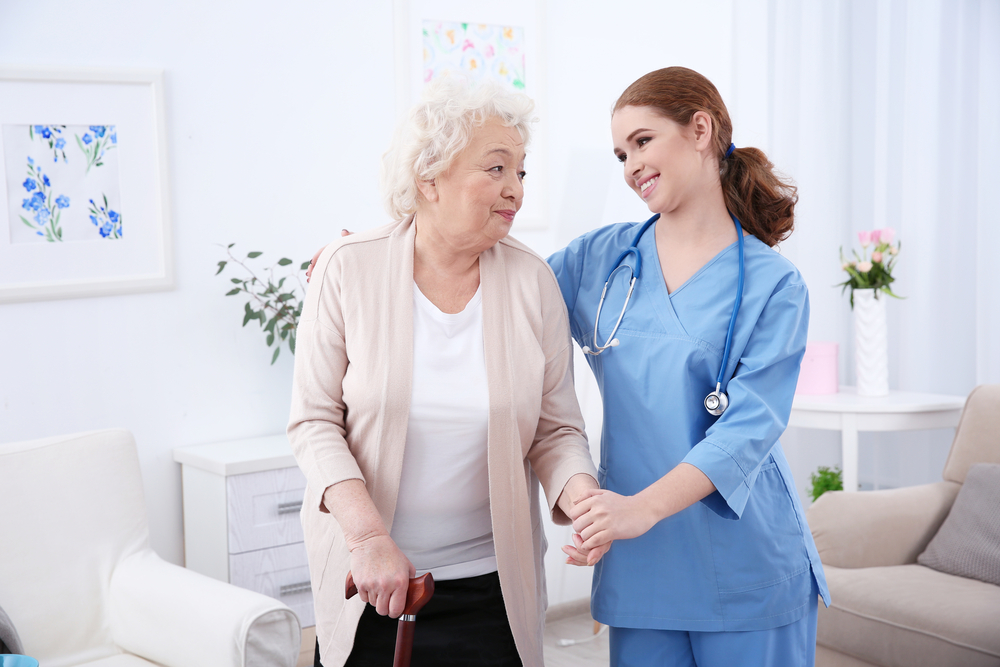 A nurse helping an old aged woman