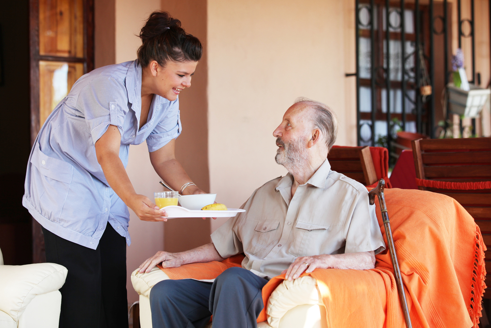 A caregiver serves food to an old aged man