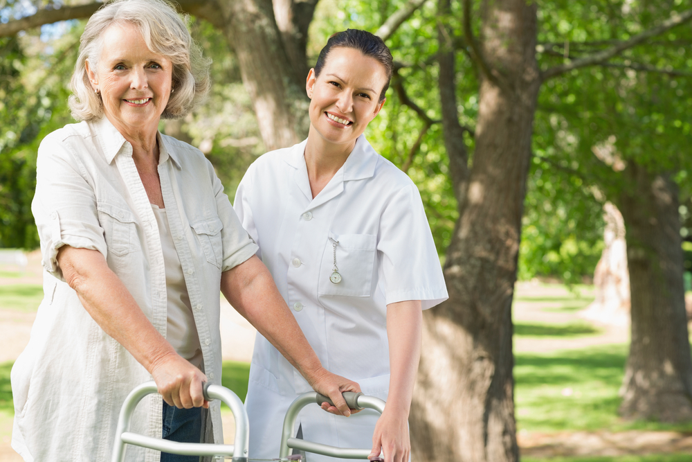 A senior lady assisted by a caregiver