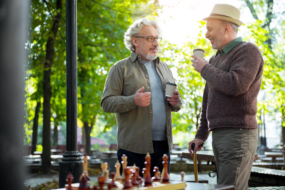 Joyful senior male friends enjoying hot beverage outdoor