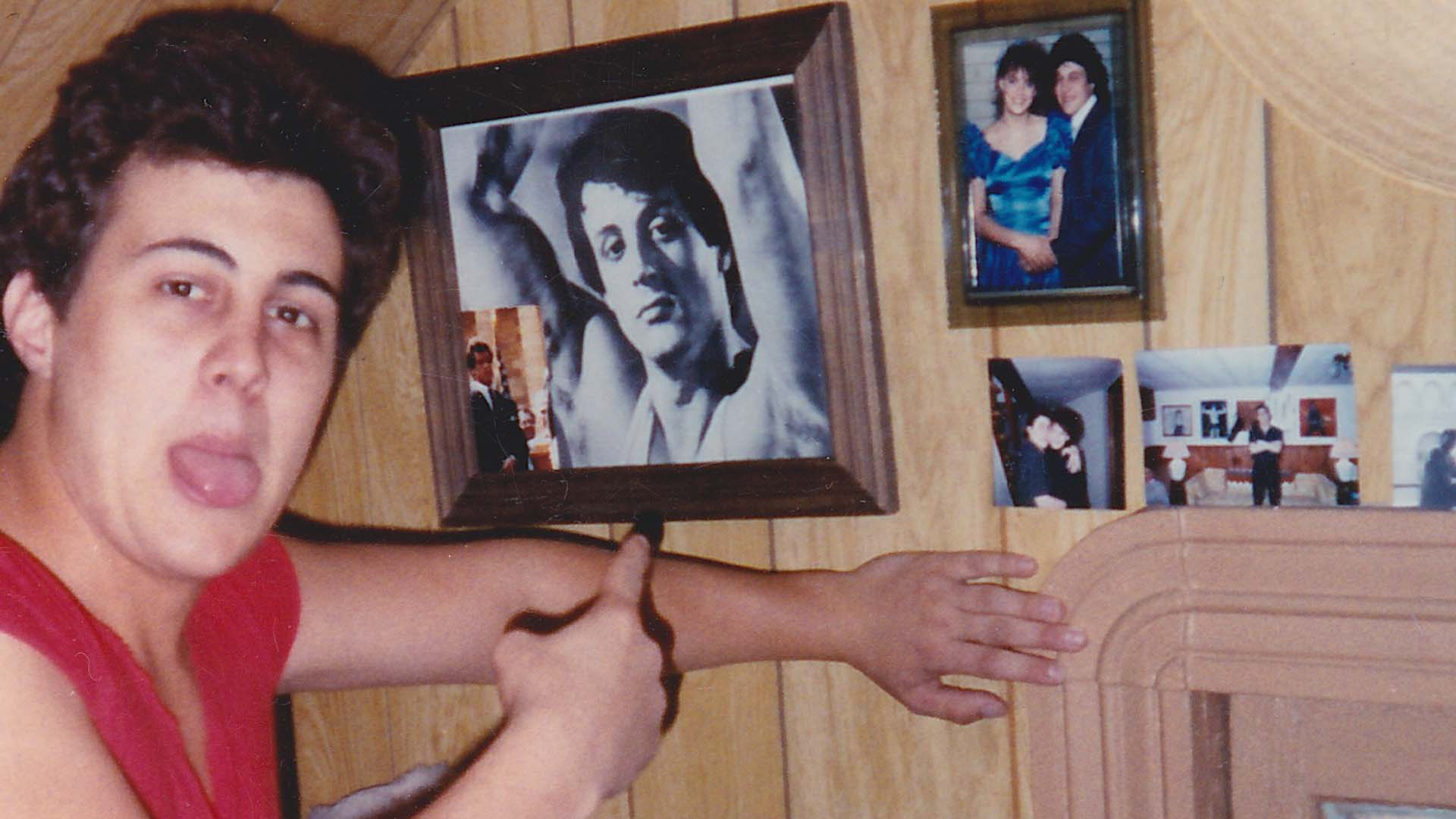 "Mike Kunda posing with ""family"" photos."