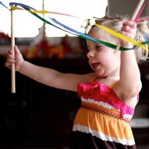 Girl enjoying streamer in toddler party