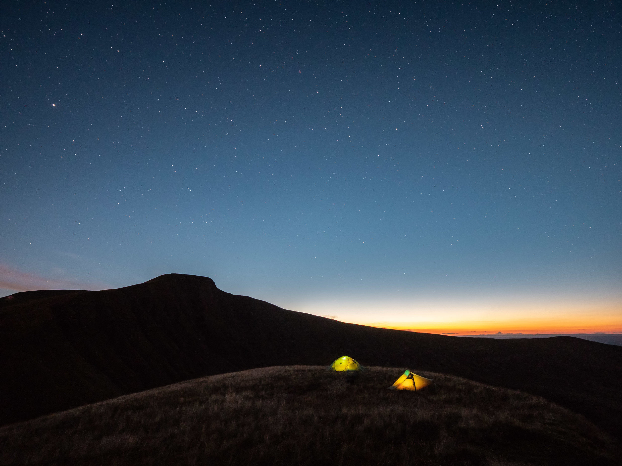 The silhouette of Pen y Fan under the stars as the last of the evening colour still lingers.