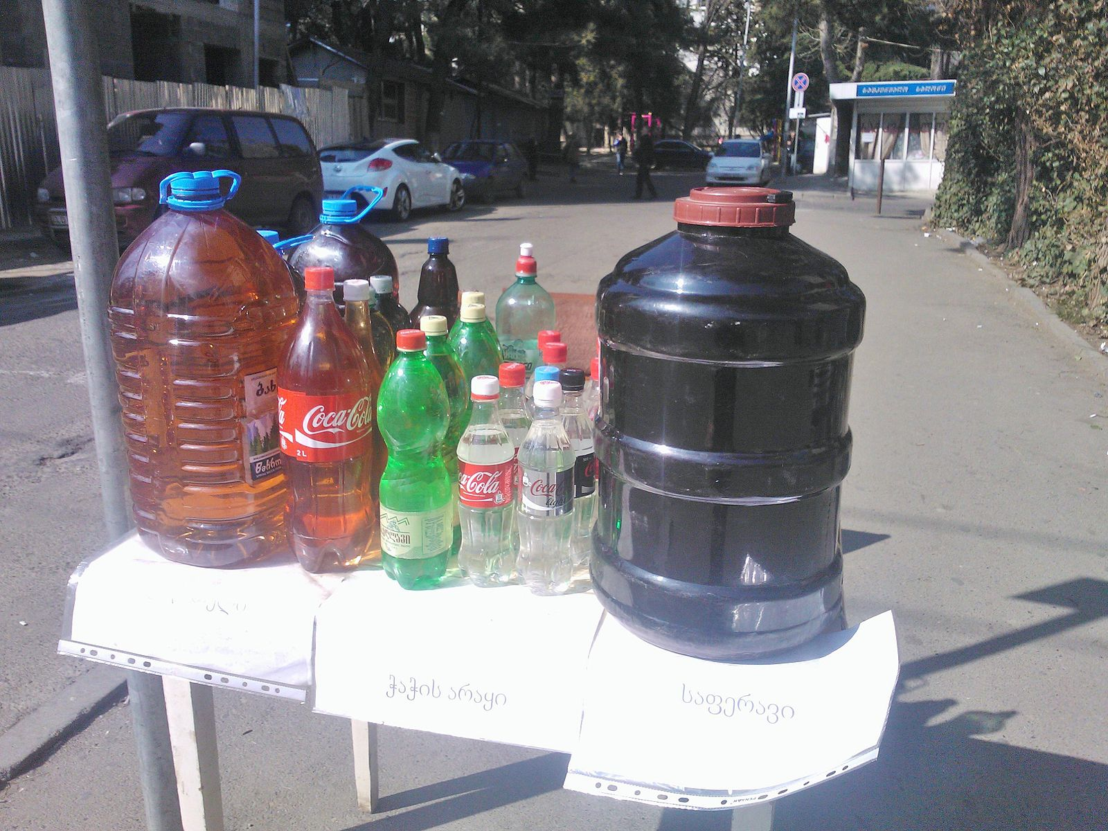 Home distilled chacha (in the middle bottles) and wine being sold in totally legit, not-at-all-dodgy bottles on the street in Tbilisi. Photo by Wikimedia Commons user Daniel-TBS.