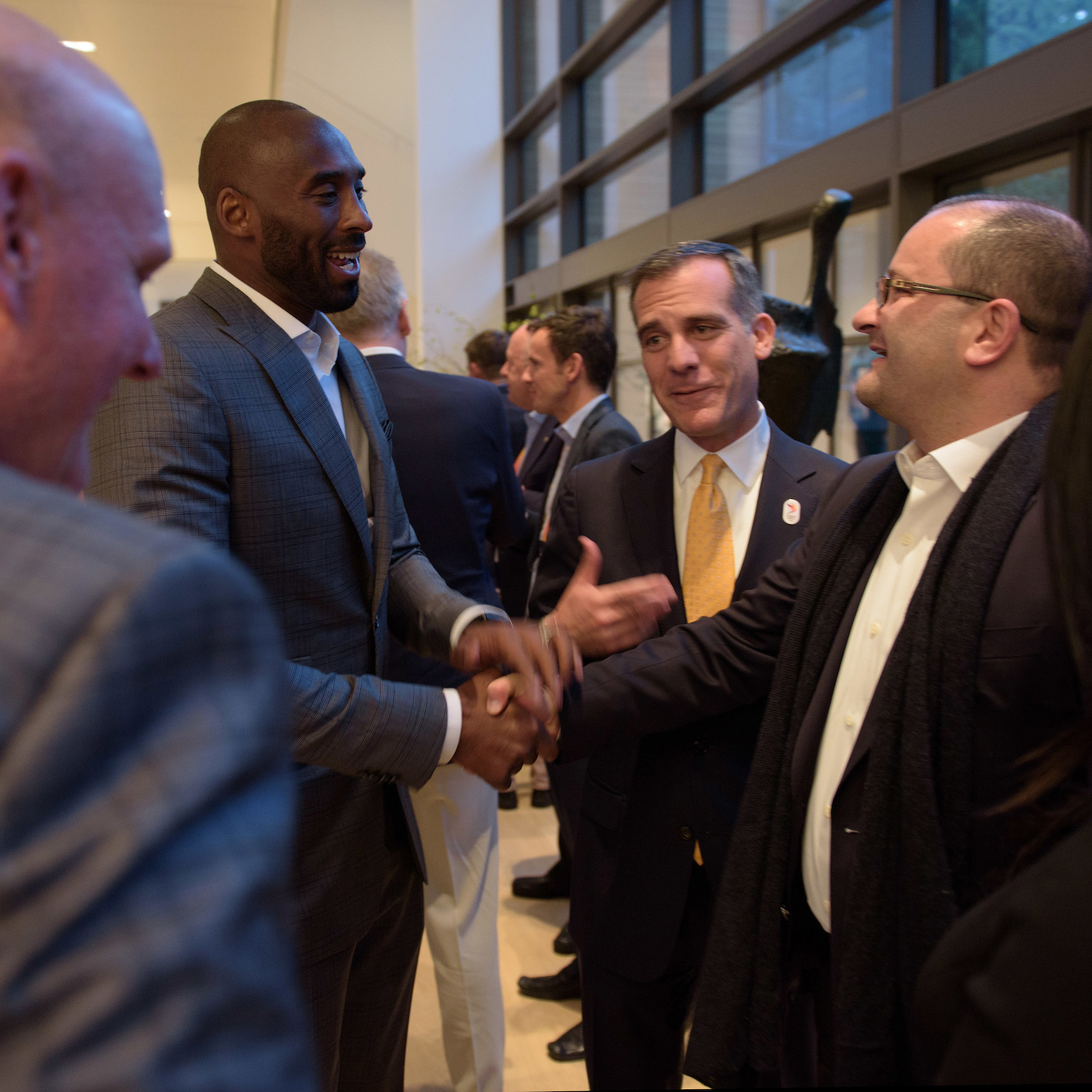 Proving, perhaps, that a communications strategy can work for everyone: Laker fans saw this guy scowl on the court for 20 years. Now Kobe Bryant is all smiles as he meets Patrick Baumann, right, LA mayor Eric Garcetti in the middle // David Lienemann/LA2024