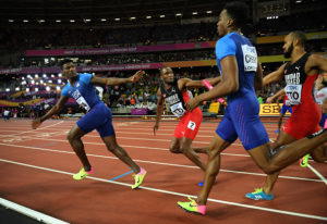 Fred Kerley, left, gets the baton from Michael Cherry during the men's 4×400 relay // Getty Images