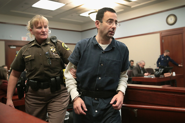 Larry Nassar being led out this week of a Lansing, Michigan courtroom // Getty Images