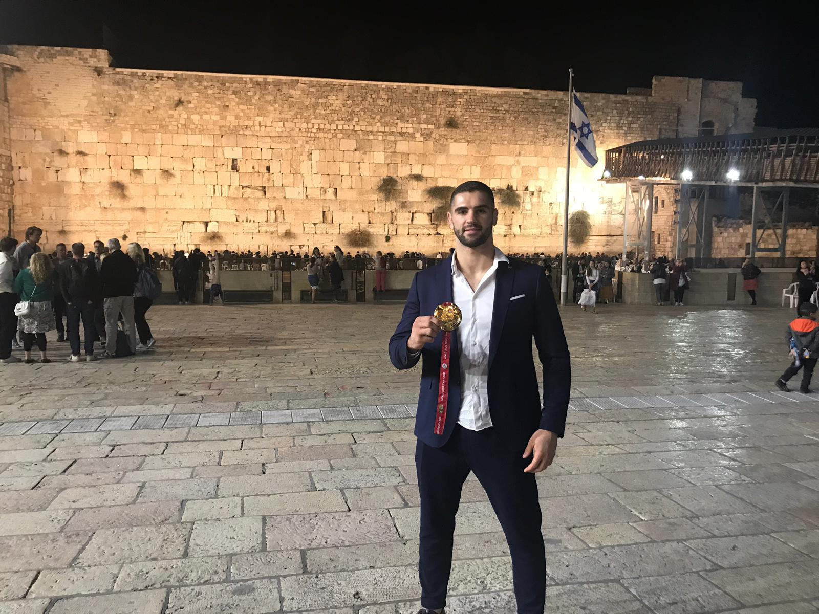 The Israeli judo athlete Peter Paltchik with the gold medal he won at the 2018 Abu Dhabi Grand Slam, in a picture taken in front of the Western Wall in Jerusalem // photo courtesy Peter Paltchik