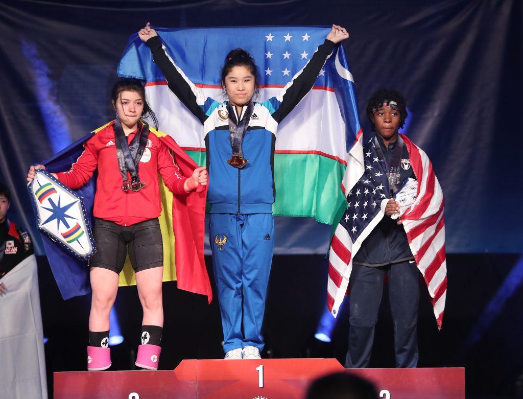 Women's 49-kilo medalists at the youth world weightlifting championships in Las Vegas, left to right — silver, Romania's Mihaela Valentina Cambei; gold, Uzbekistan's Nigora Abdullaeva; bronze, Kaiya Lashay Bryant of the United States // photo IWF