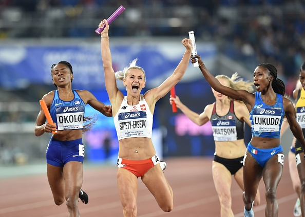 Justyna Swiety-Ersetic of Poland at the line of the women's 4x4 ahead of Courtney Okolo of the United States // KAZUHIRO NOGI/AFP/Getty Images