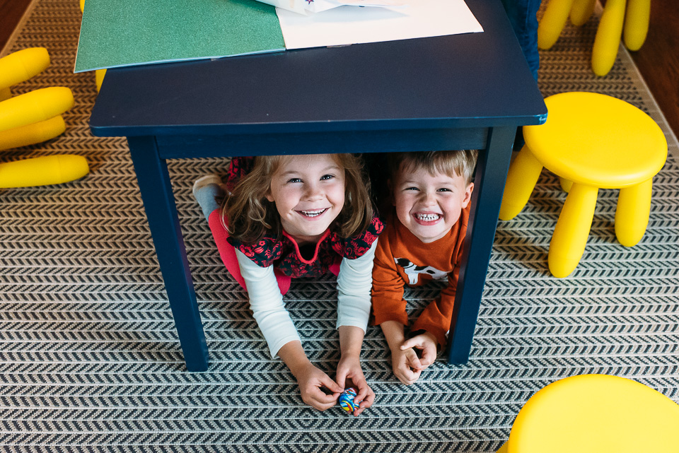 Children under a table smiling.