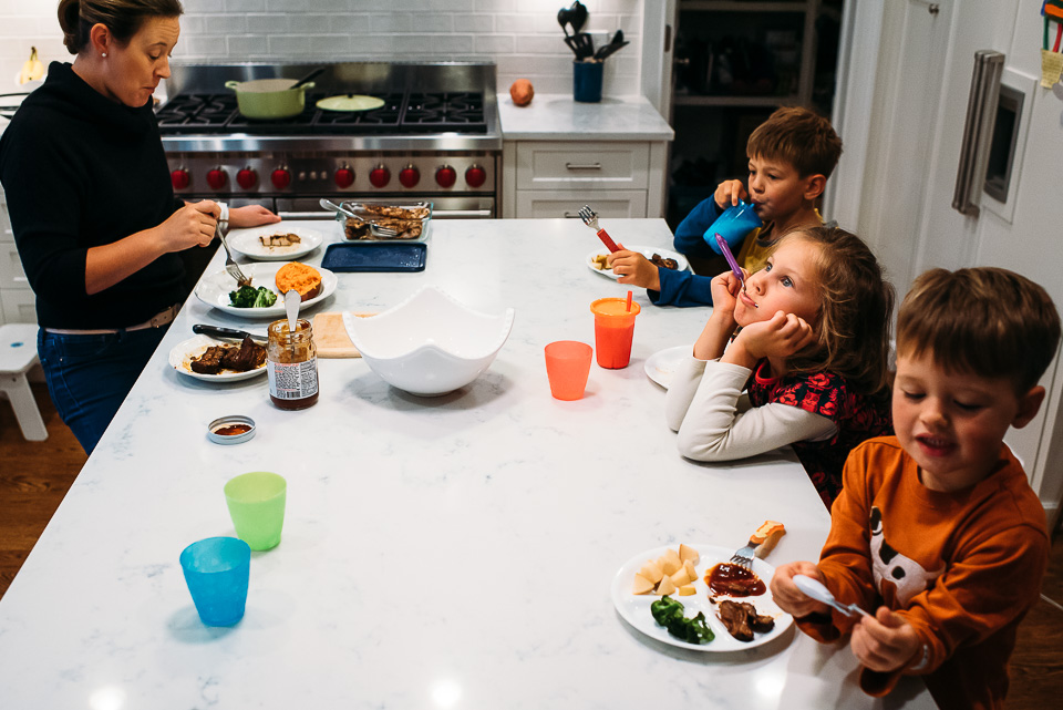 Mother eating dinner with three children.