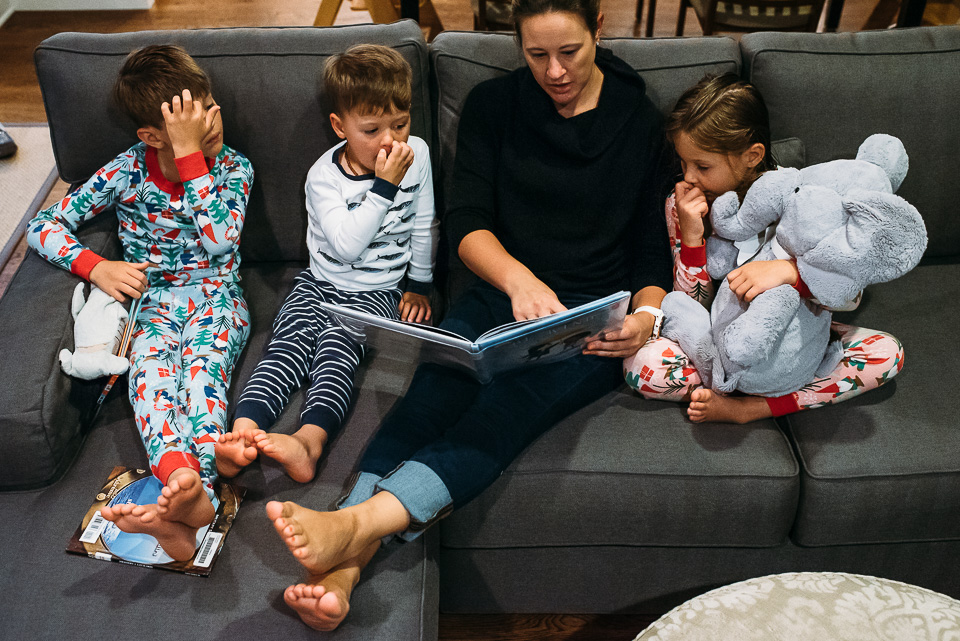 Mother reading a book to children.