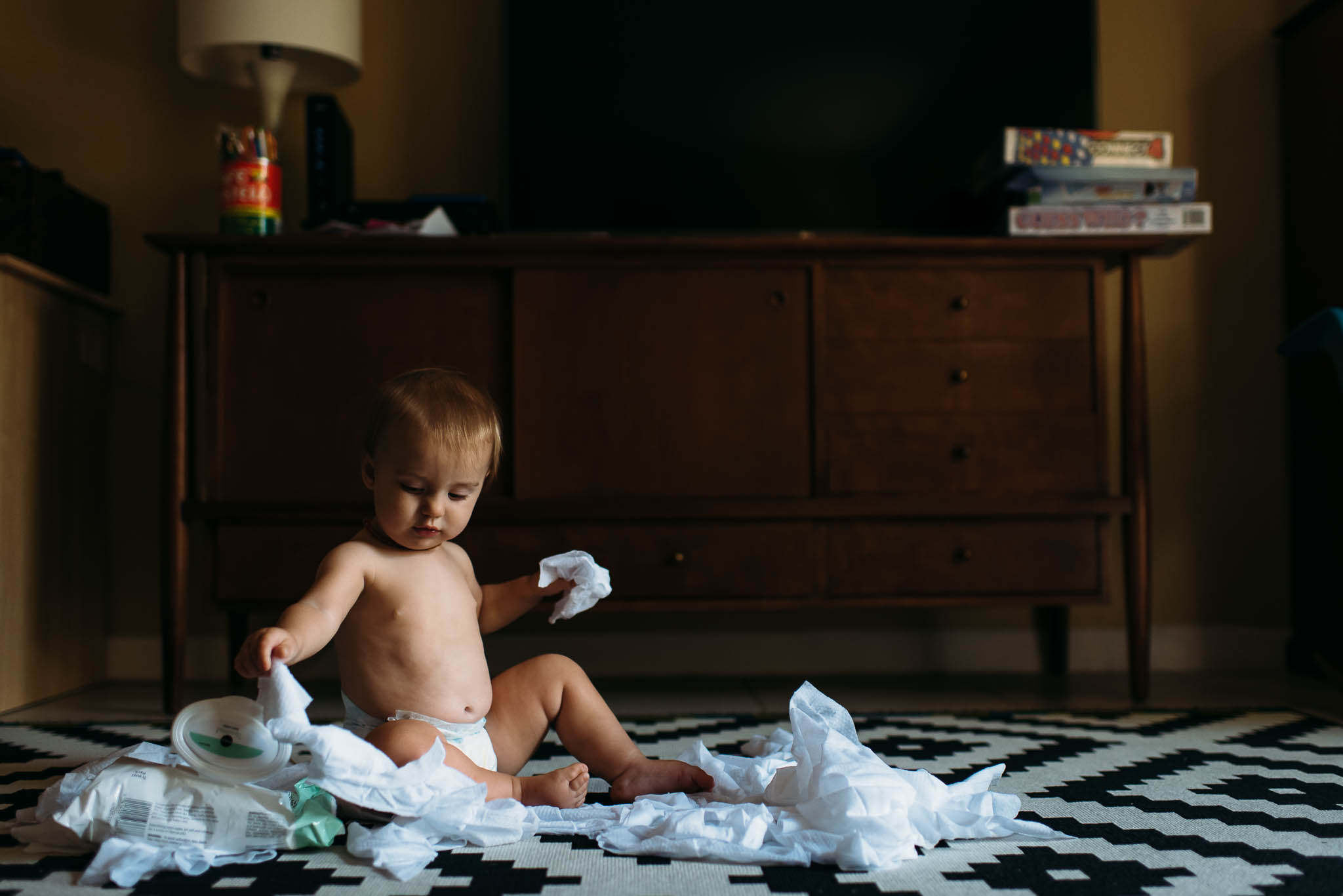 Baby pulling wipes out of a container and making a mess.