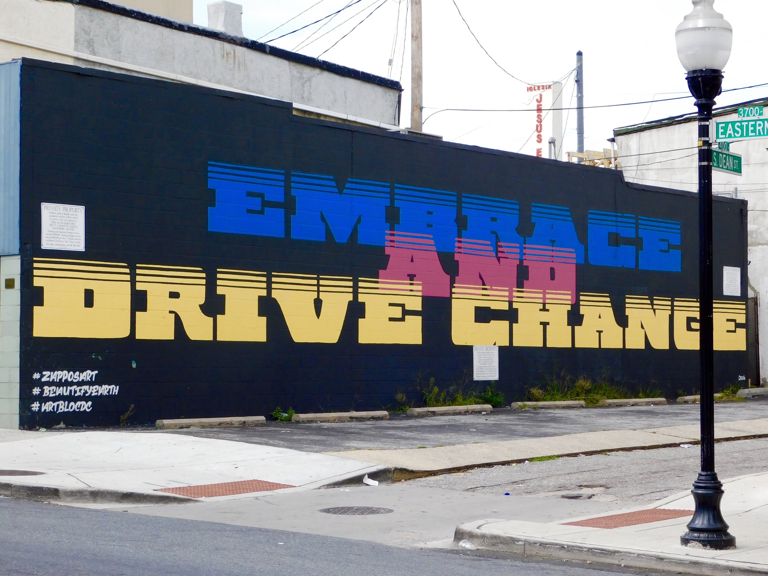 """I was recently in the Highlandtown neighborhood of Baltimore for Street Art Walk led by the artist  Michael Owen . We didn't stop to explore this piece, but I couldn't resist the message or the colors. One of the things I love about street art is that the image is just the beginning. Since most pieces, like this one, are signed or include hashtags, I try to dig into finding out about the person and context behind the work. Turns out the three hashtags revealed a lot. """"Embrace and drive change"""" is one of  Zappos' 10 Core Values . The company (thus #ZapposArt) worked with the nonprofit (#BeautifyEarth) to sponsor artists to turn their core values into murals in cities across the country. Seems like a number of the artists aren't actually home grown. In this case #ArtBlocDC is a DC-based artist. It's not uncommon for street artists to do works in other cities, or for corporations to sponsor them. However, I particularly love street art when it's a reflection of how folks are shaping the local landscapes in which they live and work.Snapped on my Nikon B500 at Eastern Ave. and S. Dean Street."""