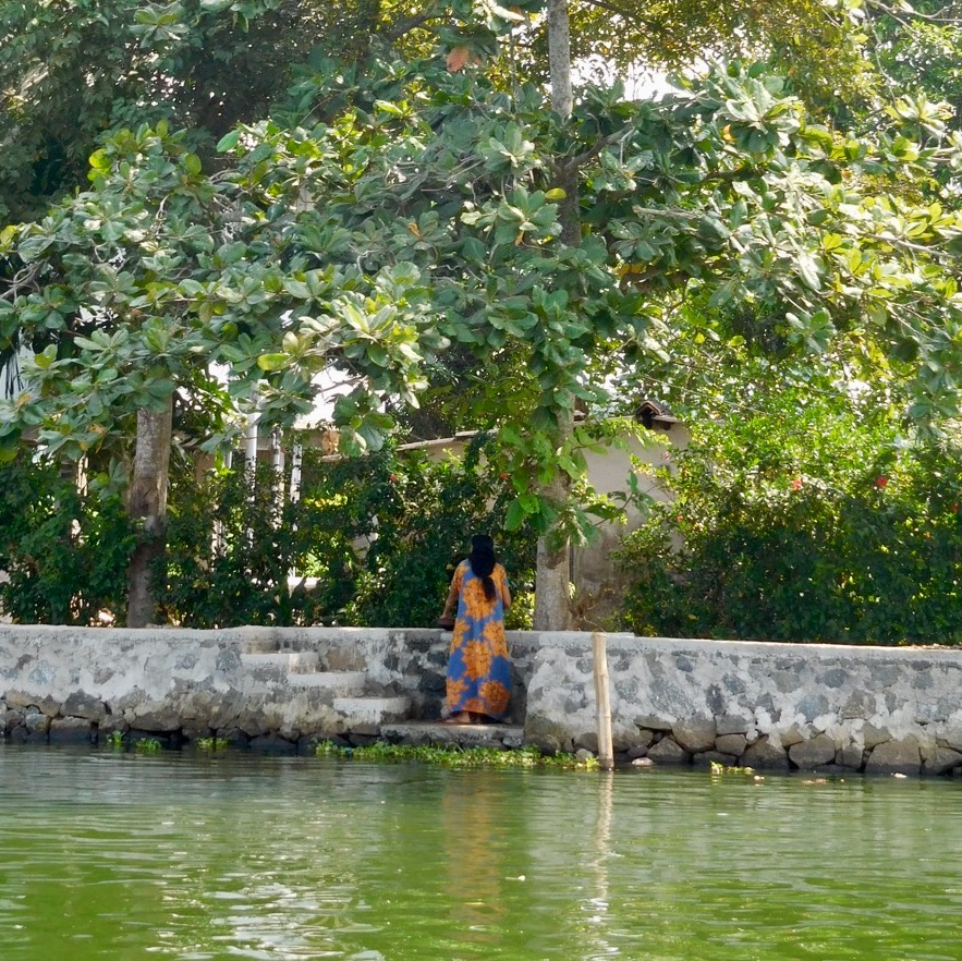 A woman on the shore of the Kerala Backwaters, India.