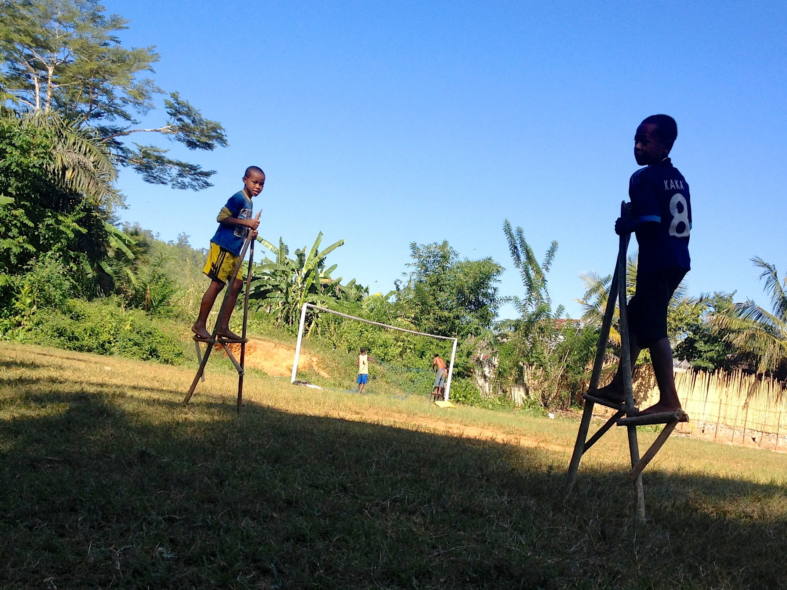 Malagasy children playing on football field before a match.