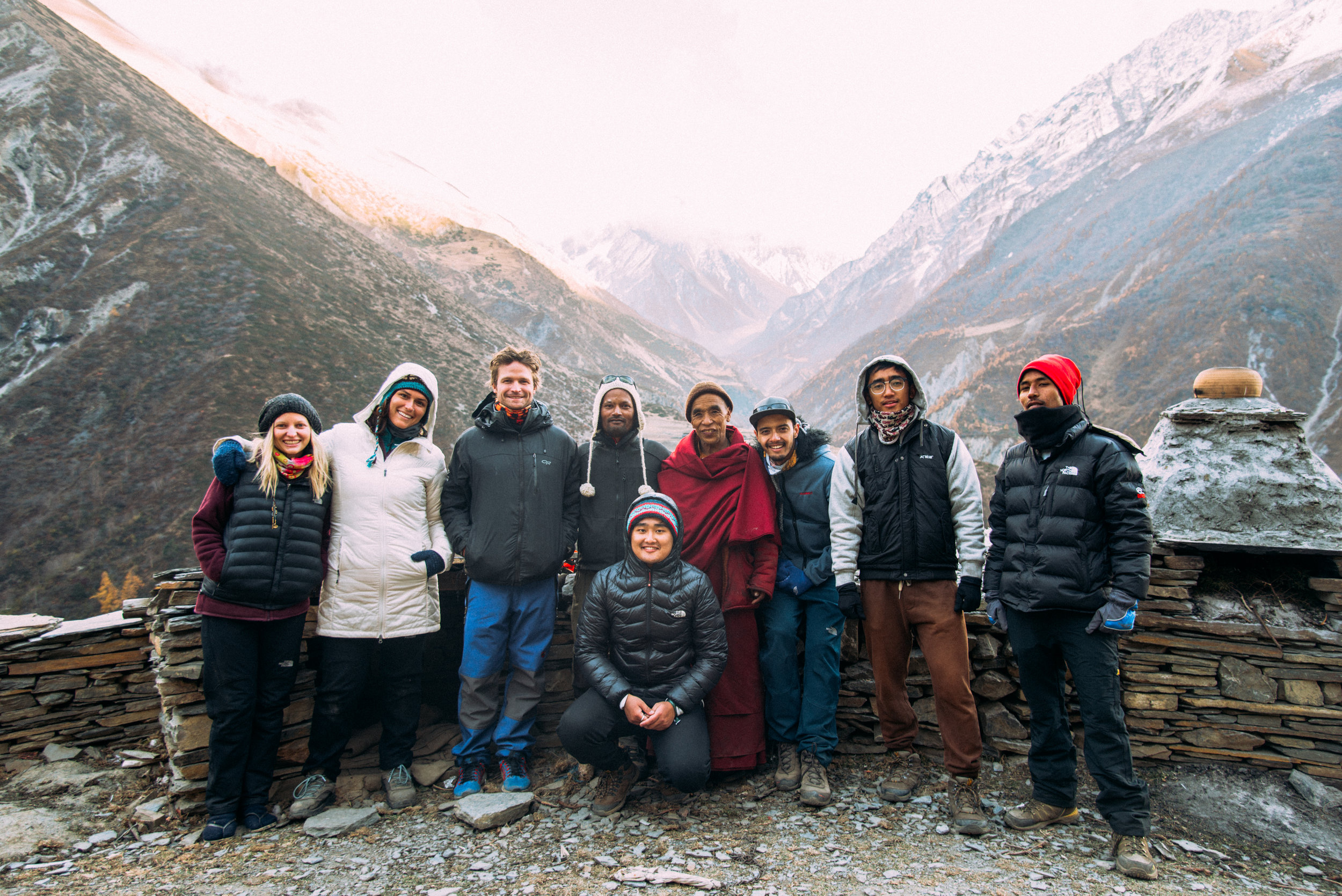 Our team of trekkers, guides, and videographers standing with one of the monks at the monastery of Mu Gompa in Tsum Valley.  Image by Jimee Lama.