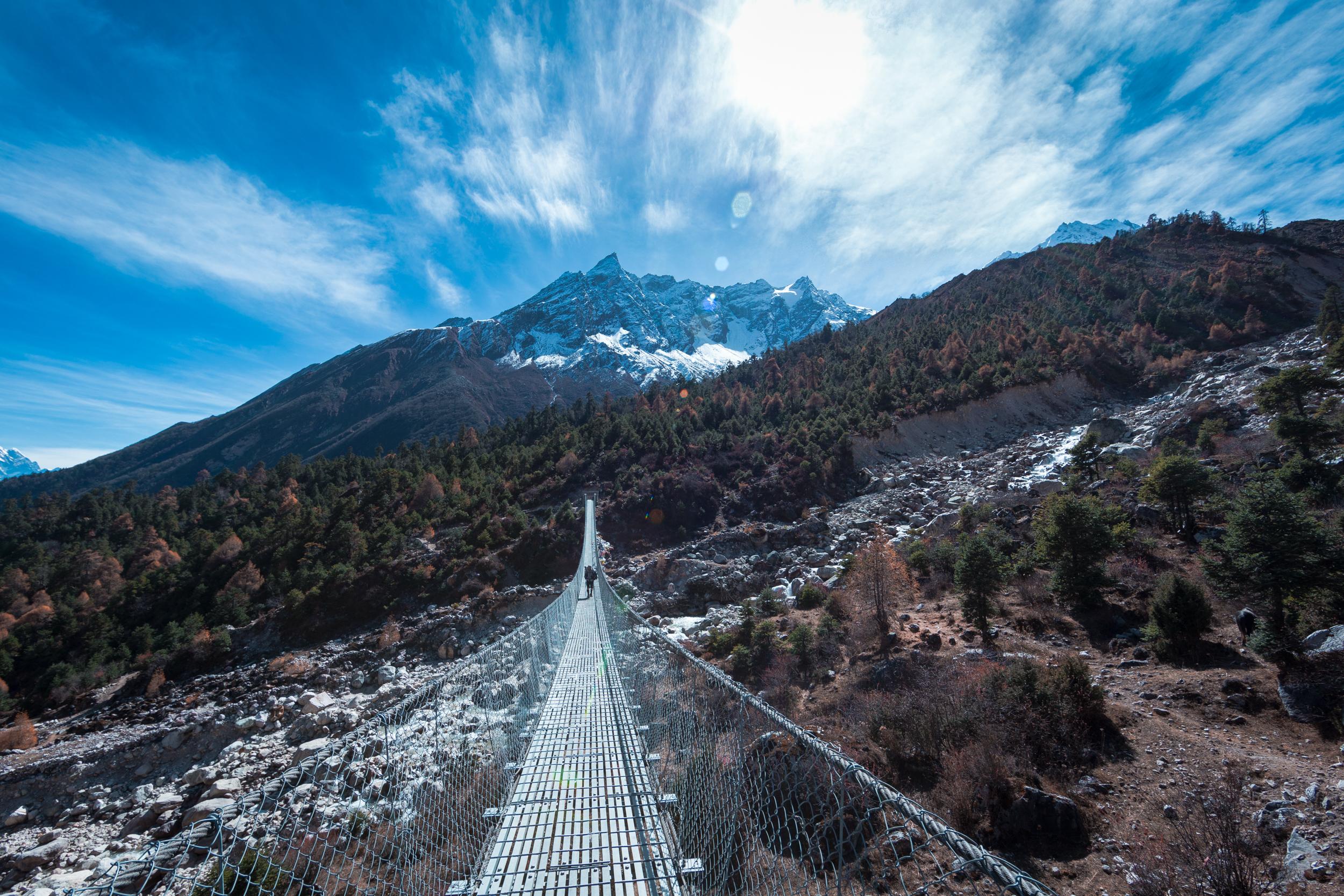 The glacial landscape across a long rope bridge.